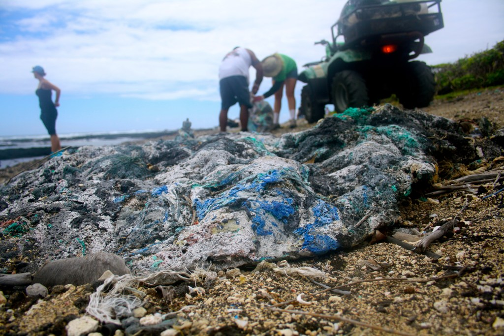 Photo of a gnarled plastic/carbon/rock item in the foreground, with people doing research in the background